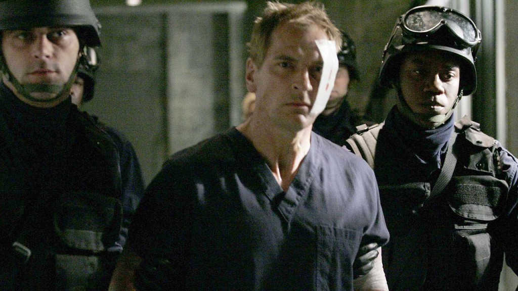 Vladimir Bierko (Julian Sands) is escorted by armed guards in 24 Season 5 Episode 21
