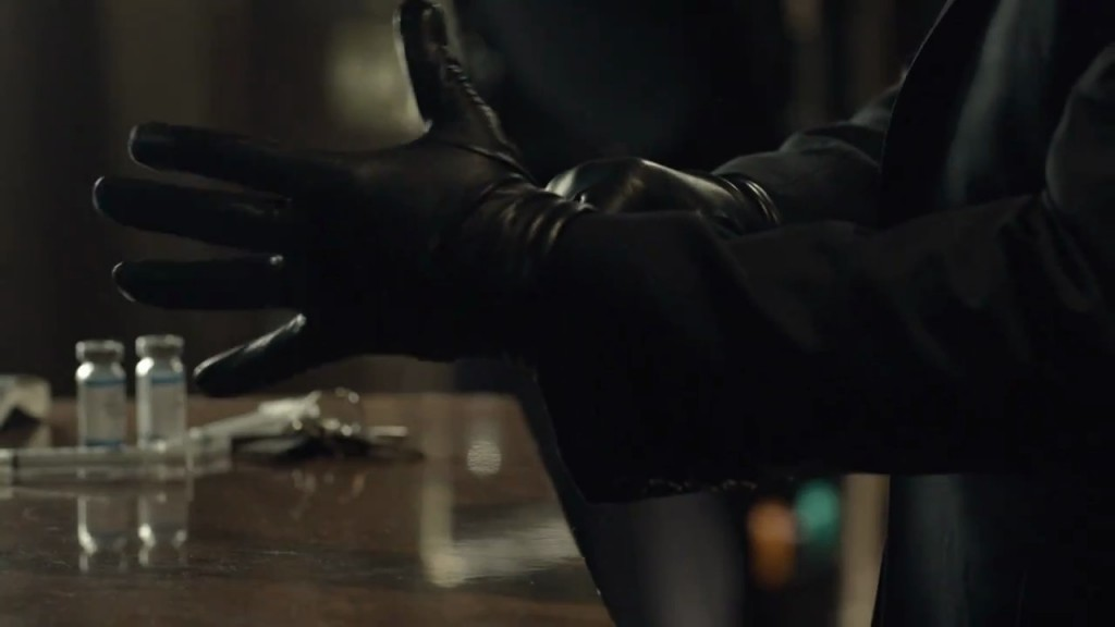 Kiefer Sutherland in The Confession putting on gloves