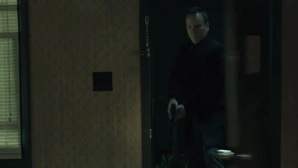Kiefer Sutherland in The Confession kicking down door holding gun