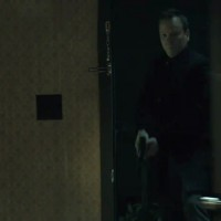 Kiefer Sutherland in The Confession kicking down door holding gun