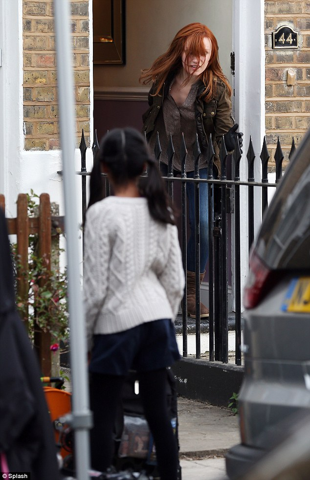 She is chasing a young girl out of a terraced house